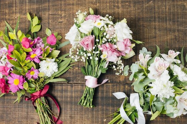 Diferentes tipos de ramos de flores atadas con cinta en el escritorio de madera