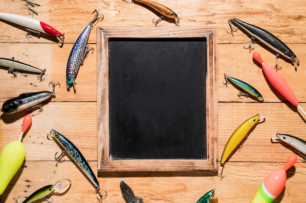 Diferentes tipos de señuelos de pesca alrededor de la pizarra de madera negra sobre fondo de madera