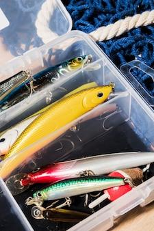 Diferentes tipos de señuelos de pesca en el contenedor blanco.