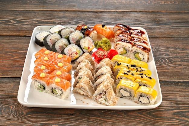 Diferentes tipos de sushi japonés en plato blanco.