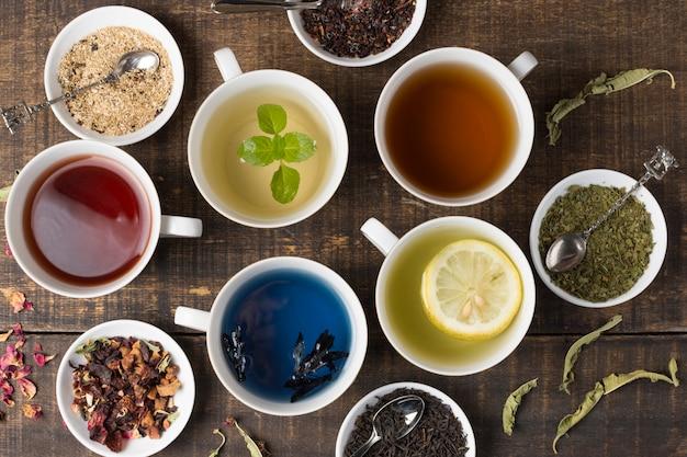Diferentes tipos de tazas de té de aroma blanco con hierbas en mesa de madera
