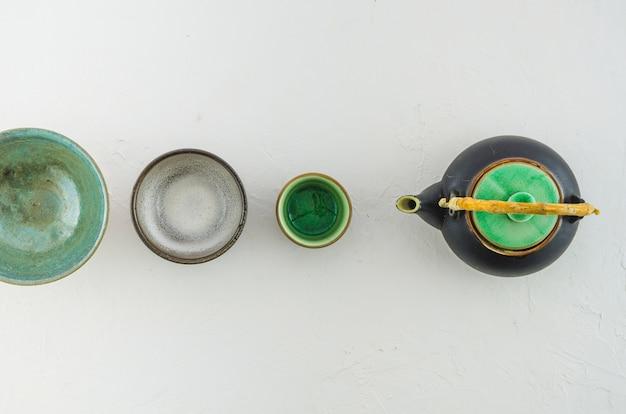 Diferentes tipos de tazas de té y tetera sobre fondo blanco