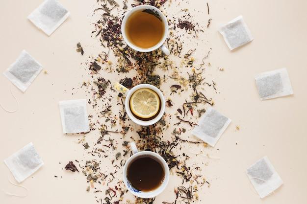 Diferentes tipos de té dispuestos en una fila con bolsita de té y hierbas sobre fondo coloreado