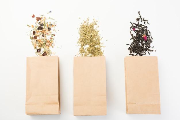 Diferentes tipos de té de hierbas derramando de una bolsa de papel marrón sobre fondo blanco