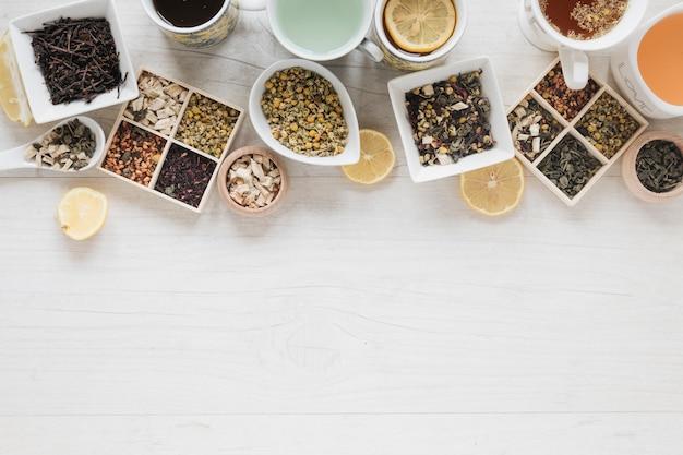 Diferentes tipos de té con hierbas y hojas secas de té en el escritorio