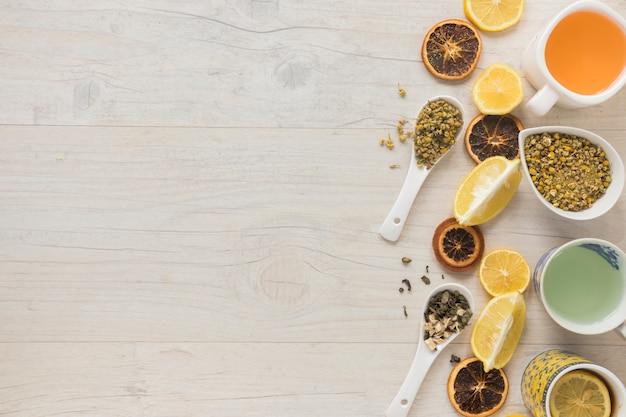 Diferentes tipos de té en taza de cerámica con hierbas y rodajas de pomelo seco en el escritorio