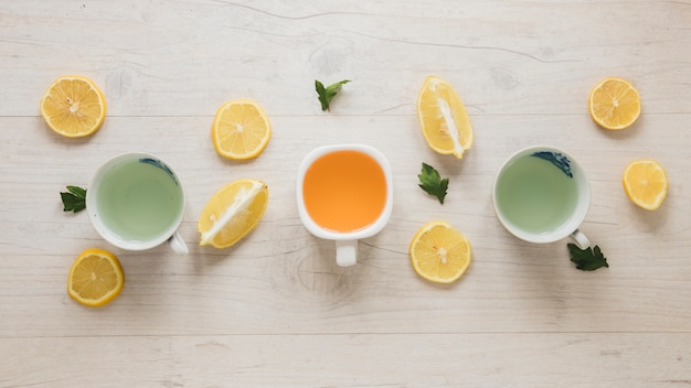 Diferentes tipos de té en taza de cerámica con hojas y rodajas de limón en mesa de madera
