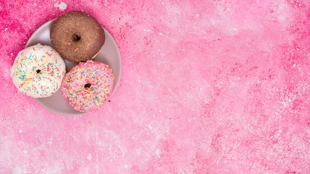 Diferentes tipos de tres donuts en acero inoxidable contra fondo rosa