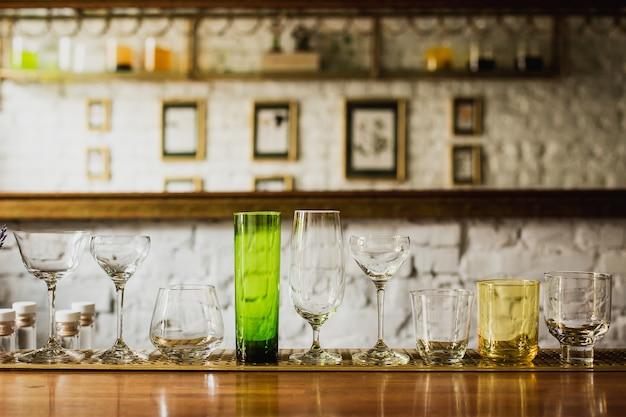 Diferentes tipos de vasos en una barra de bar, rocas, anticuados, highball, nick y nora, cupé Foto Premium