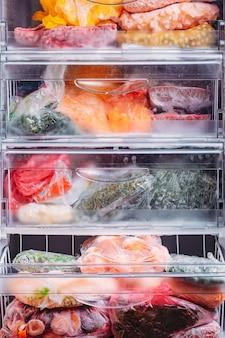 Diferentes tipos de verduras congeladas en bolsas de plástico en un refrigerador