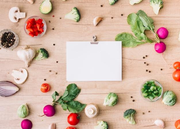 Diferentes tipos de verduras frescas con papel blanco en blanco se adjuntan con un clip