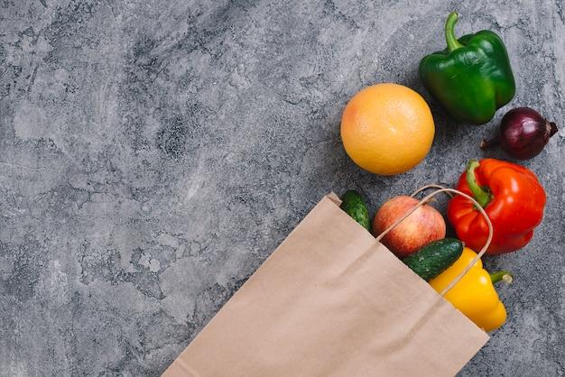 Diferentes tipos de verduras y frutas en el piso gris degradado.