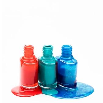 Diferentes tonos de esmalte de uñas se derramaron alrededor de tres botellas abiertas