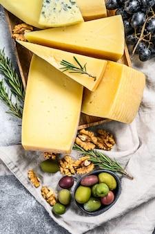 Diferentes trozos de queso con nueces, aceitunas y uvas. surtido de deliciosos aperitivos. fondo gris vista superior