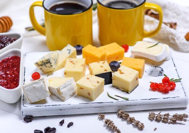 Diferentes trozos de queso sobre una plancha de madera blanca.