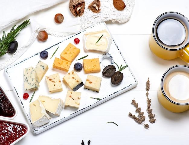 Diferentes trozos de queso en una tabla de madera blanca y dos tazas amarillas con una bebida