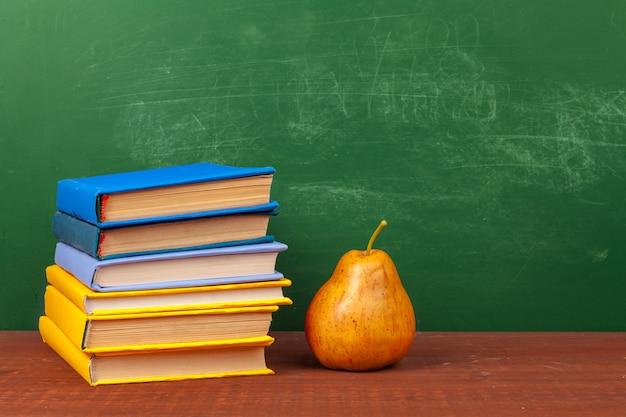 Diferentes útiles escolares, libros y pera en mesa de madera