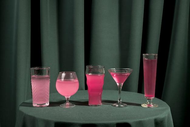 Diferentes vasos llenos de líquido rosa sobre mesa.