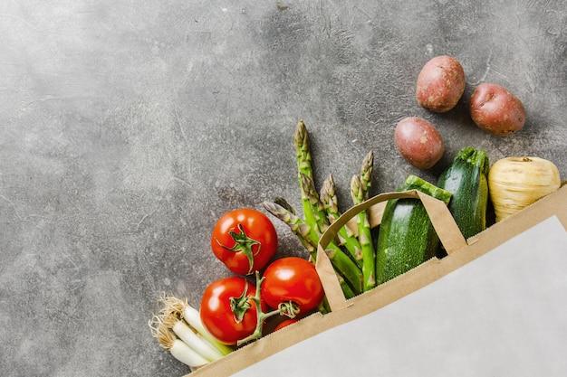 Diferentes vegetales en bolsa de papel sobre gris.
