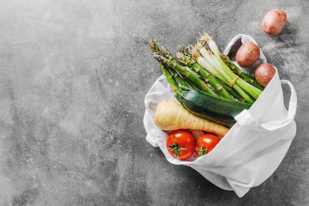 Diferentes vegetales en bolsa textil en gris.