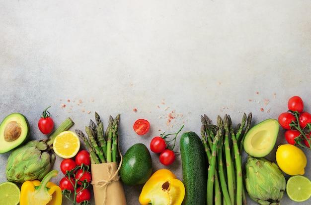 Diferentes vegetales orgánicos: espárragos, tomates, cerezas, aguacates, alcachofas, pimientos, limas, limones, sal sobre fondo gris.