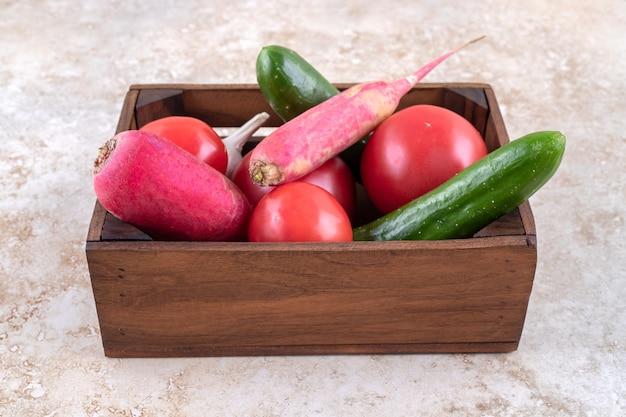 Diferentes verduras en una caja, sobre la mesa de mármol.