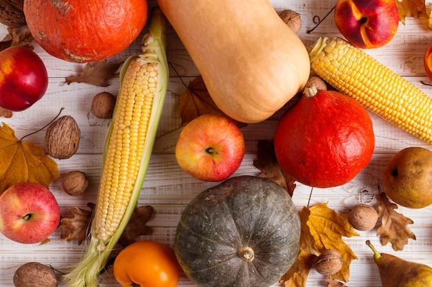 Diferentes verduras calabazas, manzanas, peras, nueces, maíz, tomates, hojas amarillas secas sobre fondo blanco de madera. cosecha de otoño, copyspace.