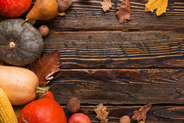 Diferentes verduras, calabazas, manzanas, peras, nueces, tomates, maíz, hojas amarillas secas sobre fondo de madera. humor de otoño, copyspace. cosecha