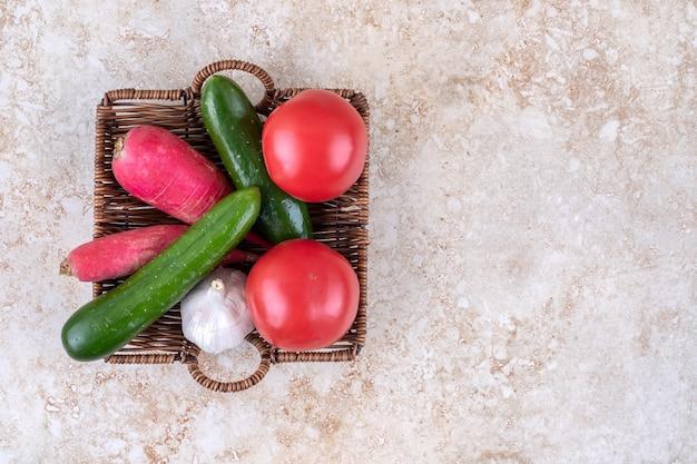 Diferentes verduras en una canasta de mimbre, sobre la mesa de mármol.