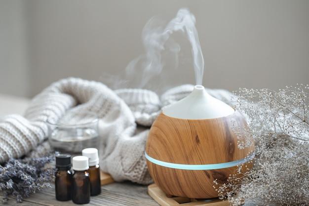 Difusor de aceite aromático moderno sobre superficie de madera con elemento tejido, agua y aceites en frascos.