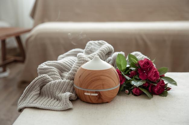 Difusor de aroma de aceite moderno en el salón sobre la mesa con elemento de punto y flores.
