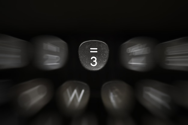 Dígito en tecla negra en máquina de escribir retro con fondo borroso