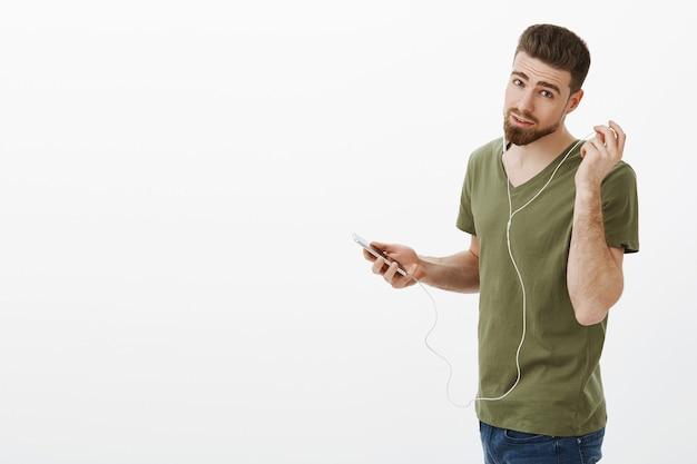 Dijiste algo. retrato de guapo novio parado profily en metro girando y tomando auriculares mientras pregunta qué persona quería decir sosteniendo teléfono inteligente sobre pared blanca