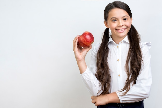 Diligente colegiala hispana comiendo manzana
