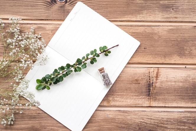 Diminutas flores blancas con tallo y flor de lavanda botella en el cuaderno sobre el fondo de madera