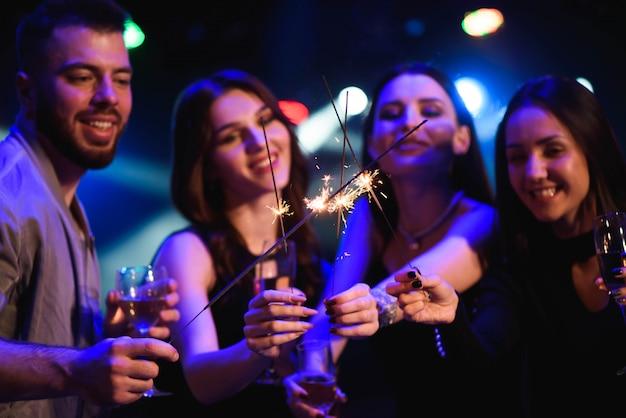 Dinámicos jóvenes amigos bailando en la fiesta disco