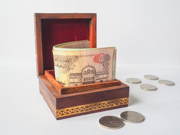 Dinero árabe dirhams en la vieja caja de madera.