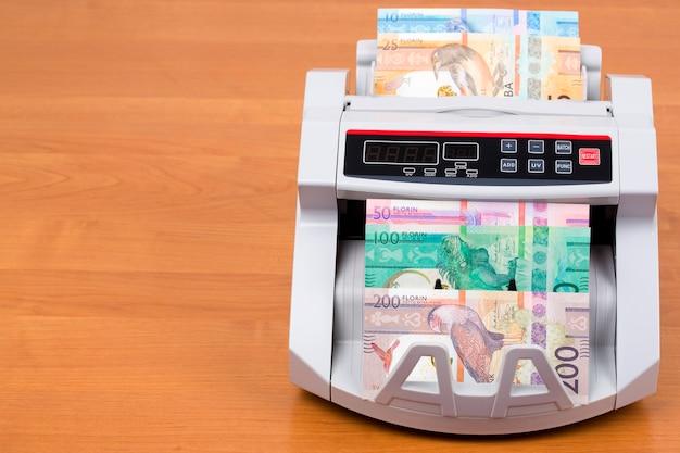 Dinero de aruba - florin en la máquina de contar