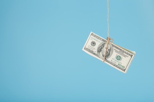 Dinero atado dólares en una cuerda, en un azul.