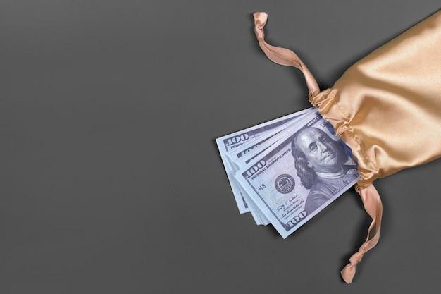 Dinero en bolsa de regalo dorada sobre gris