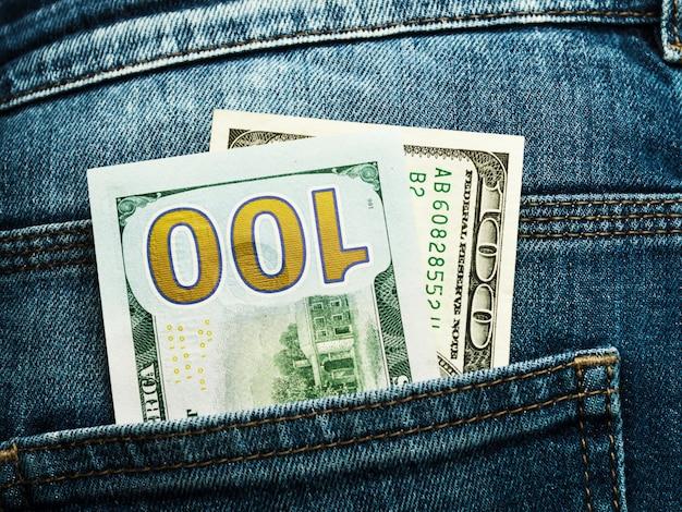 Dinero en el bolsillo de los jeans, dos billetes de cien dólares