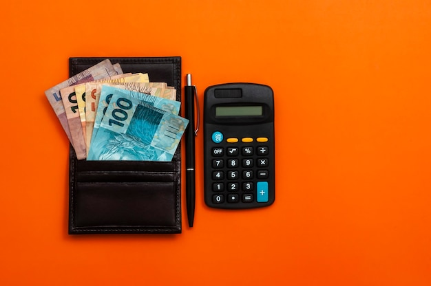 Dinero brasileño en billetera, con bloc de notas, bolígrafo y calculadora.