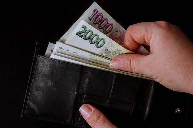 Dinero checo en manos de una mujer sobre un fondo negro.