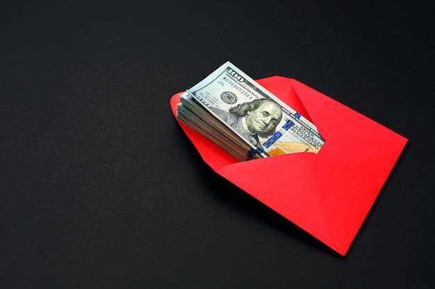 Dinero en dólares en el sobre rojo sobre negro