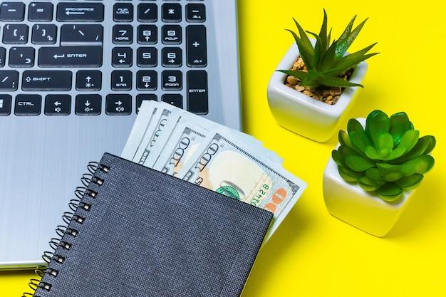 Dinero ganado en forma independiente en un cuaderno sobre una superficie amarilla