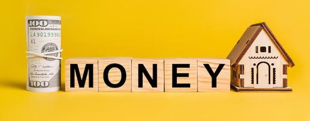 Dinero con modelo de casa en miniatura y dinero sobre un fondo amarillo.