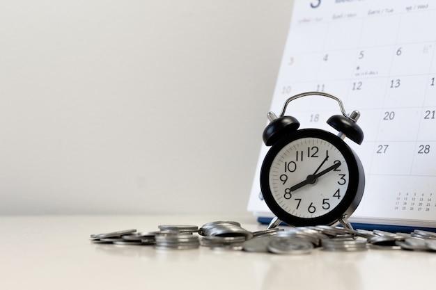 Dinero monedas paso con calendario y reloj despertador copia espacio para texto