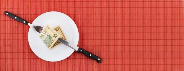 Dinero en plato con tenedor y cuchillo. concepto financiero y empresarial.