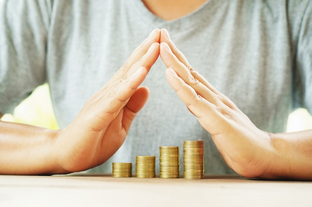 Dinero de la protección del hombre de negocios en el ahorro del concepto de la tabla