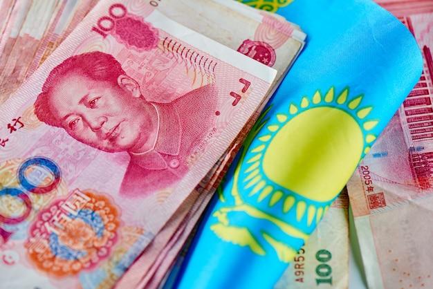 Dinero yuan chino en la bandera de kazajstán. países asiáticos y concepto de relaciones de mercado